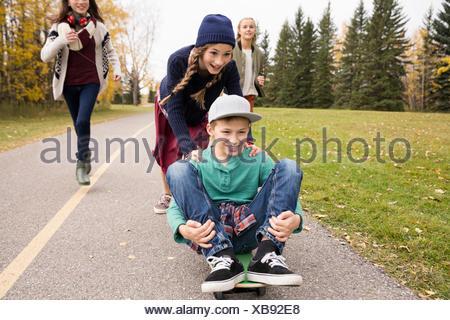 Tween boy e le ragazze lo skateboard sul percorso in autunno park Foto Stock