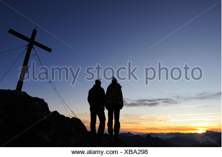 Giovane donna e giovane uomo godersi il tramonto al vertice di Risserkogel, Prealpi bavaresi, montagne Mangfall, Baviera, Germania Foto Stock