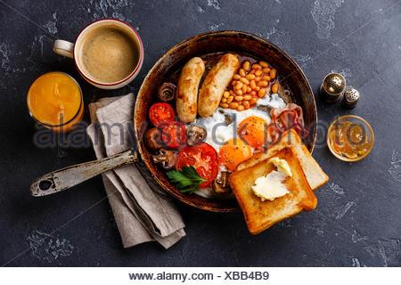 Prima colazione inglese in padella con uova fritte, salsicce, pancetta, fagioli, pane tostato e caffè scuri su sfondo di pietra Foto Stock