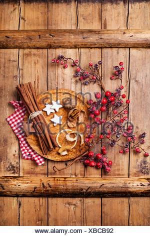 Biscotti natalizi, noci, essiccato a buccia d'arancia, bastoncini di cannella e il ramo con bacche rosse su legno sfondo texture Foto Stock