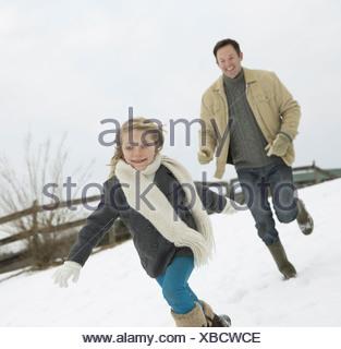Un uomo a caccia di una giovane ragazza nella fattoria di neve in inverno Foto Stock