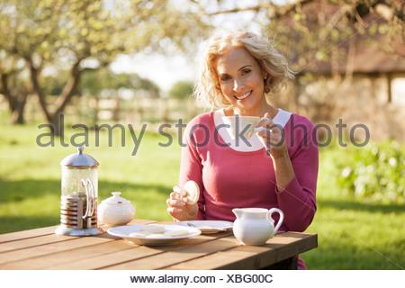 Una donna matura con caffè e biscotti in un giardino Foto Stock