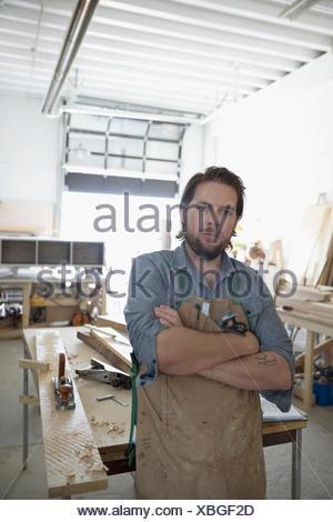 Ritratto fiducioso falegname maschio nel piazzale di sosta in officina Foto Stock