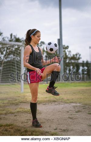 Giocatore di calcio la pallina che rimbalza sul ginocchio in campo Foto Stock