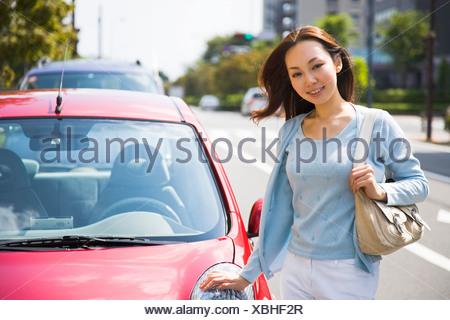 Giovane donna in piedi accanto a AUTO Foto Stock