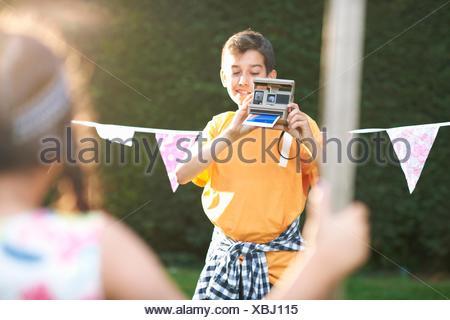 Ragazzo ragazza di fotografia utilizzando la fotocamera istantanea