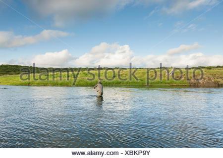 L'uomo per la pesca del salmone in un bellissimo circondario Foto Stock