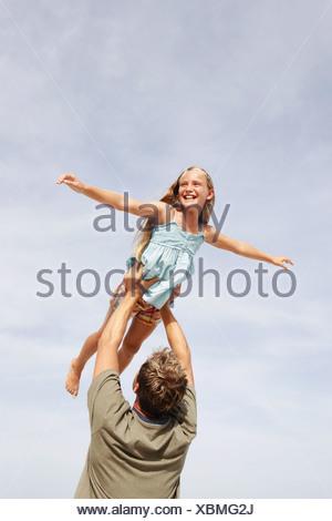 Padre figlia di sollevamento in aria Foto Stock