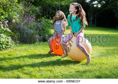 Proprietà rilasciato. Modello rilasciato. Due sorelle rimbalzare sul bouncy tramogge in giardino. Foto Stock