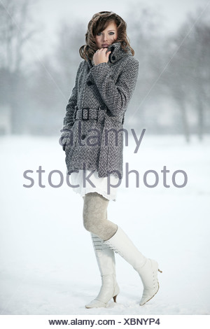 Ritratto di una giovane donna nella neve, la sua mano che tiene il suo cappotto collare Foto Stock