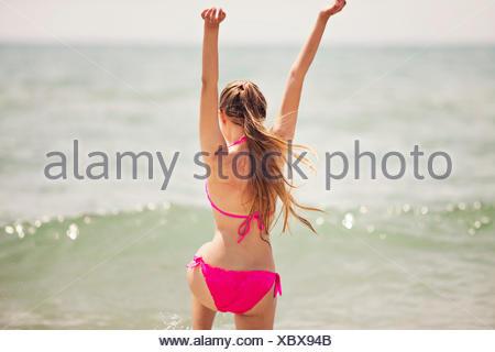 Ragazza adolescente il salto in aria sulla spiaggia Foto Stock