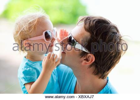 Giovane padre e figlia piccola sul suo braccio felicemente che ognuno guarda negli occhi dell'altro attraverso i loro occhiali da sole Foto Stock