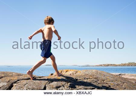 La Svezia, Uppland, Runmaro, Barrskar, ragazzo (6-7) in esecuzione sulle rocce vicino al mare Foto Stock