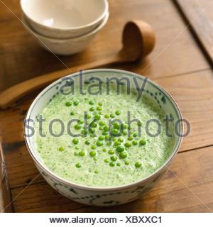 Refrigerati lattughe minestra in una ciotola con piselli sulla parte superiore Foto Stock