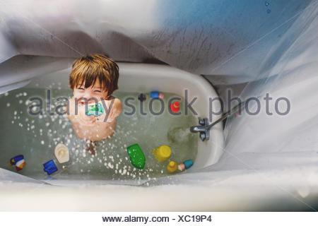 Ragazzo (2-3) giocando con i giocattoli in vasca da bagno Foto Stock