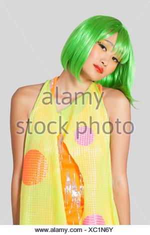 Ritratto di funky giovane donna verde seduta per capelli Foto Stock