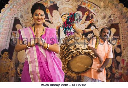 Bengali donna in piedi in una posizione di preghiera e una riproduzione di Dhaki Dhak a Durga Puja Foto Stock