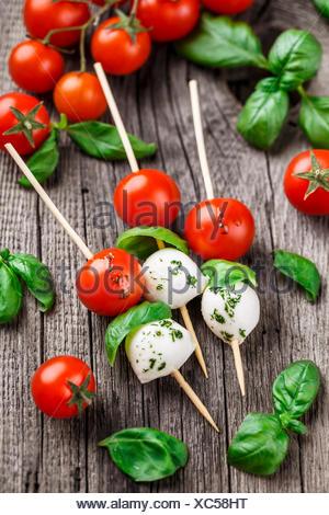 Spiedini con pomodoro, basilico e mozzarella su un sfondo rustico Foto Stock