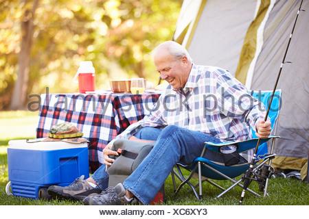 Senior uomo sulla vacanza in campeggio con la canna da pesca Foto Stock