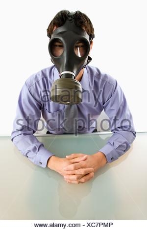 Imprenditore seduto in camera bianca indossando maschera a gas Foto Stock