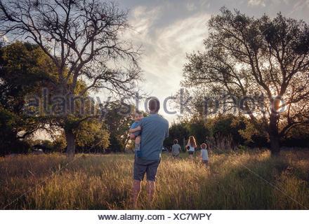 Padre e quattro bambini passeggiate nel paesaggio rurale al crepuscolo, Texas, America, STATI UNITI D'AMERICA Foto Stock