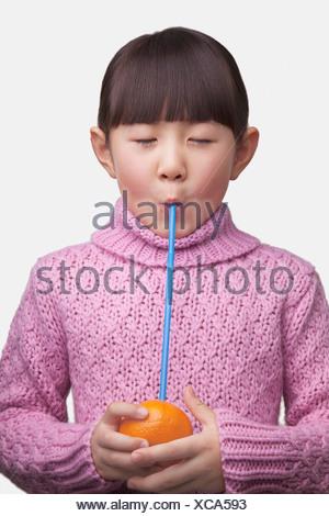 Ritratto di giovane ragazza di bere un arancione con una cannuccia, studio shot Foto Stock