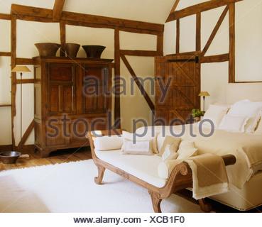 https://l450v.alamy.com/450vit/xcb1f0/il-xvi-secolo-e-credenza-stile-impero-di-dormeuse-nel-paese-di-travi-di-camera-da-letto-con-letto-imbottito-e-tappeto-bianco-xcb1f0.jpg