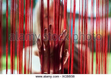 Donna che mette la mano attraverso una tenda frangia
