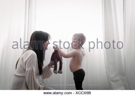 Un fortemente incinta Donna che gioca con il suo giovane figlio. Foto Stock