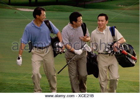 Tre uomini che trasportano le sacche da golf in un campo da golf Foto Stock