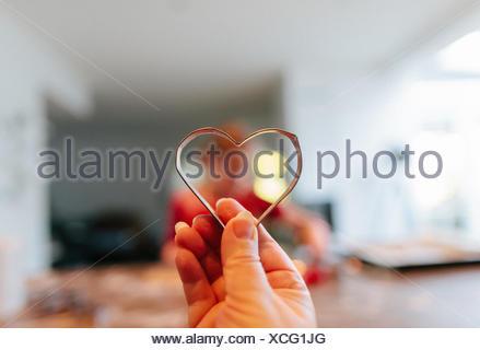 Mano azienda forma di cuore formina nella parte anteriore di una ragazza la cottura Foto Stock
