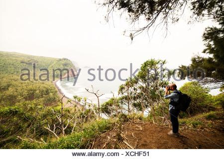 Metà uomo adulto fotografare la linea costiera Foto Stock