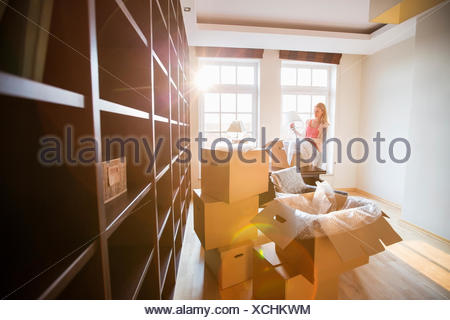 Donna di disimballare la lampada dalla scatola di movimentazione a casa nuova Foto Stock