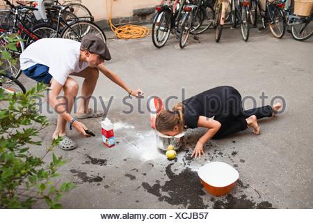 Bambini che giocano con il cibo sul marciapiede Foto Stock
