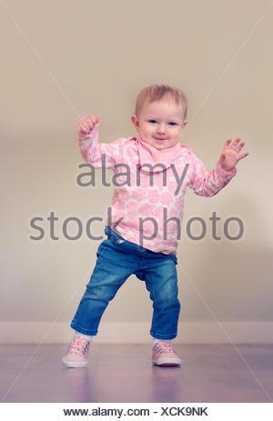 Baby girl tenendo i suoi primi passi Foto Stock