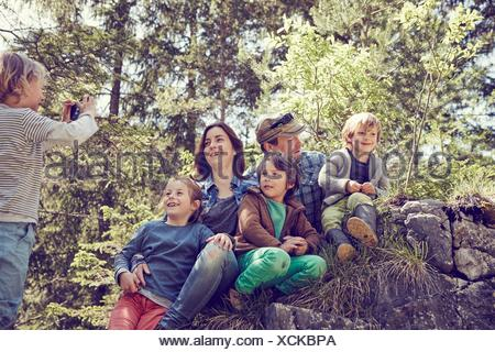 Ragazzo giovane tenendo fotografia di famiglia, nella foresta Foto Stock