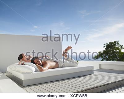L uomo e la donna sdraiata sul letto in esterni con cielo blu Foto Stock