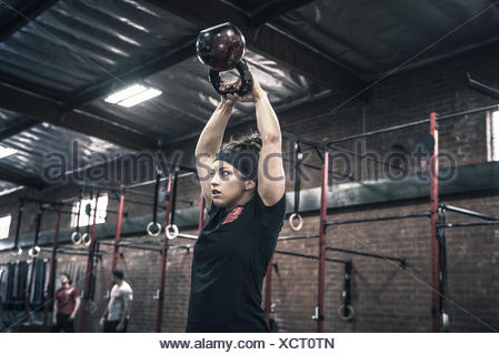 Giovane donna tenendo alto il bollitore campane in palestra Foto Stock