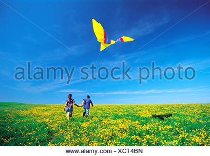 I bambini in esecuzione con kite attraverso il campo di lupolina, Winnipeg, Manitoba, Canada Foto Stock