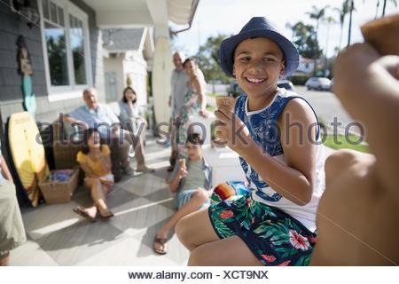 Ragazzo sorridente a mangiare il gelato cono con la famiglia in estate spiaggia casa portico Foto Stock