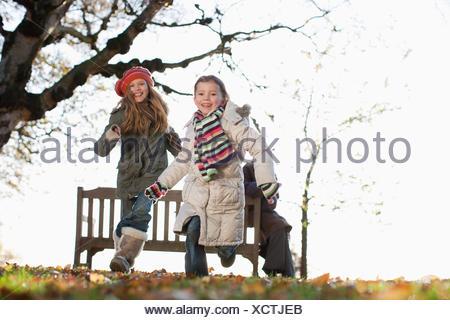 Due sorelle giocare all'aperto in autunno Foto Stock