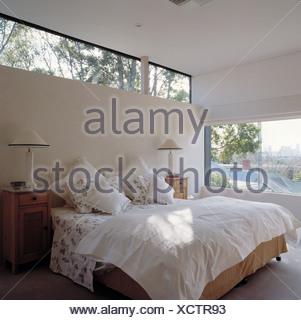 Finestra stretta sopra il letto con lenzuola bianche in bianca e ...