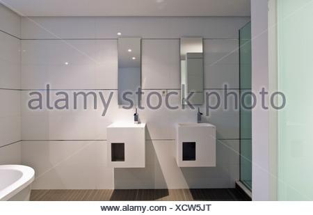 Specchio rettangolare sopra doppi lavandini bianchi in un