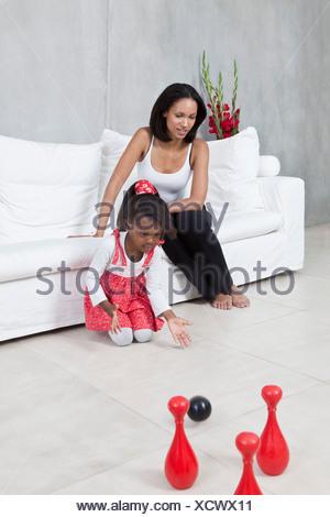 Una giovane ragazza che gioca con un giocattolo bowling impostato mentre la sua mamma orologi Foto Stock