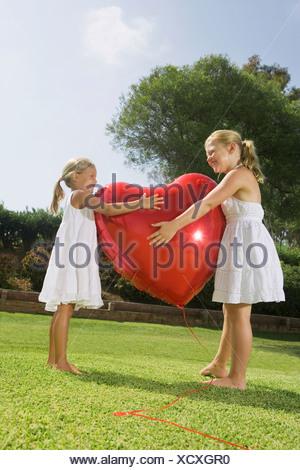 Le giovani ragazze che abbraccia cuore rosso palloncino Foto Stock