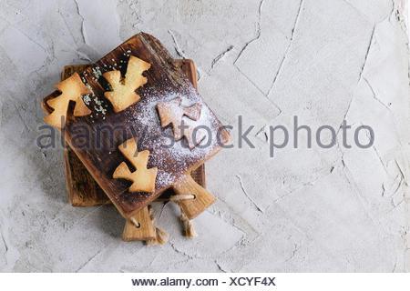 Frollini biscotti di Natale per tazze di zucchero in polvere sul piccolo tagliere di legno su grigio superficie intonacata. I cookie di forme Foto Stock