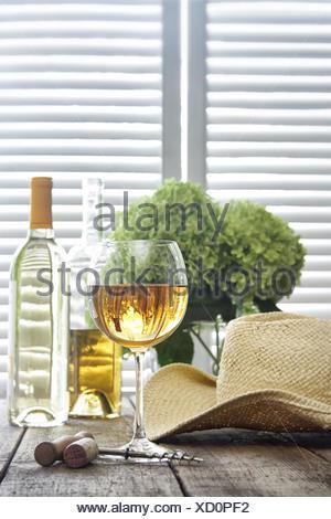 ... Bicchiere di vino in piedi su un vecchio tavolo con cappello di paglia  Foto Stock d66d59e42c0c