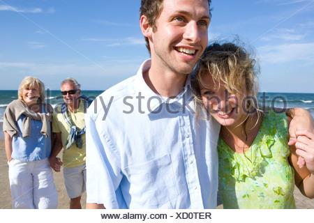 Coppia giovane camminando sulla spiaggia coppia senior in background Foto Stock