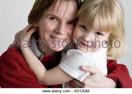 Bambina abbracciando la mamma e guardando la telecamera Foto Stock