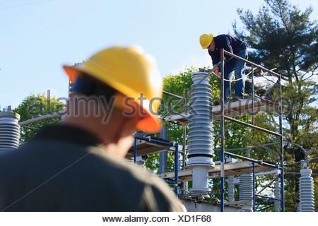 Ingegnere di potenza di eseguire interventi di manutenzione sul riempito di fluido di isolatore per alta tensione, Braintree, Massachusetts, STATI UNITI D'AMERICA Foto Stock